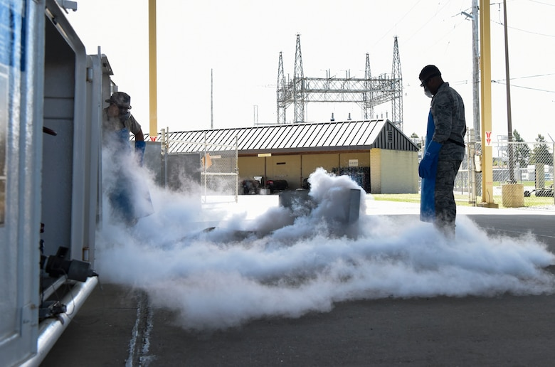 Staff Sgt. Jason Hill, 436th Logistics Readiness Squadron NCO in-charge of Fuels Facilities and Airman 1st Class Dimitrios Russell, 436th LRS cryogenics operations, perform a demonstration for an honorary commanders' tour May 9, 2018, at Dover Air Force Base, Del. Aside from seeing the abilities of cryogenics the group also toured the installation's fuels facilities. (U.S. Air Force photo by Airman 1st Class Zoe Wockenfuss)