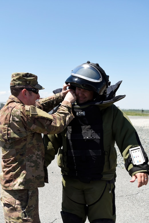 Master Sgt. Garth Muenter, 512th Civil Engineer Squadron explosive ordnance disposal technician, affixes a helmet to Allen Carter, director of business administration at Dover Motorsports, who tried on EOD protective equipment during an honorary commanders' tour May 9, 2018, at Dover air Force Base, Del. The suit weighs about 75 pounds and limits the wearer's dexterity. (U.S. Air Force photo by Airman 1st Class Zoe Wockenfuss)