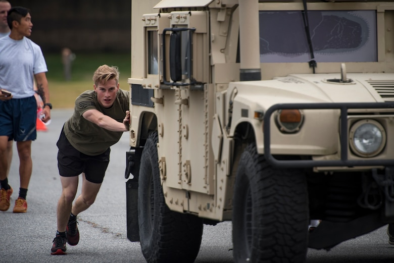 An Airman from the 822nd Base Defense Squadron pushes a Humvee during Moody's celebration of Police Week, May 14, 2018, at Moody Air Force Base, Ga. Police Week is celebrated in May of each year and is a national effort to recognize and honor law enforcement members who have lost their lives in the line of duty. Moody's 2018 celebration includes a security forces muster, a 5k run, a vehicle showcase with vehicles from the Valdosta Police Department and the Georgia State Patrol as well as memorial ceremonies. (U.S. Air Force photo by Staff Sgt. Ryan Callaghan)