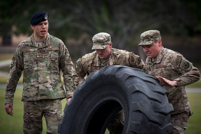 Airmen from the 824th Base Defense Squadron flip a tire during Moody's celebration of Police Week, May 14, 2018, at Moody Air Force Base, Ga. Police Week is celebrated in May of each year and is a national effort to recognize and honor law enforcement members who have lost their lives in the line of duty. Moody's 2018 celebration includes a security forces muster, a 5k run, a vehicle showcase with vehicles from the Valdosta Police Department and the Georgia State Patrol as well as memorial ceremonies. (U.S. Air Force photo by Staff Sgt. Ryan Callaghan)