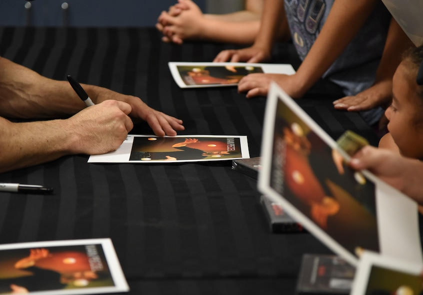 Ivan Pecel, juggler, signs autographs following his show at the Welch Theater at Keesler Air Force Base, Mississippi, May 9, 2018. Pecel, an award winning juggler with more than 15 years of juggling experience, is also a comedian and performed during the first season of America's Got Talent. The 81st Force Support Squadron and The Air Force Services Activity hosted the event. (U.S. Air Force photo by Kemberly Groue)