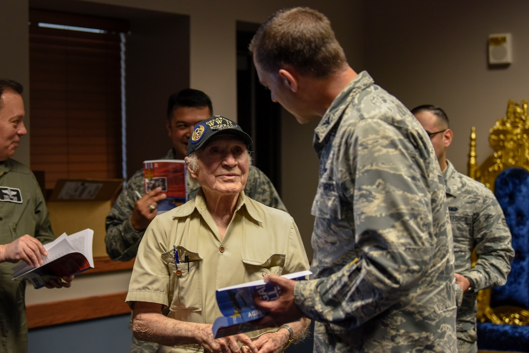 """Col. Ethan Griffin, 436th Airlift Wing commander, gets his copy of """"Against All Odds: The Firmani Story"""" signed by retired Army Air Corps 1st Lt. Ray Firmani, World War II B-17 pilot, during the quarterly Hangar Talk May 10, 2018, at Dover Air Force Base, Del. The book is an account of Firmani's experiences as a pilot during World War II. (U.S. Air Force photo by Airman 1st Class Zoe M. Wockenfuss)"""
