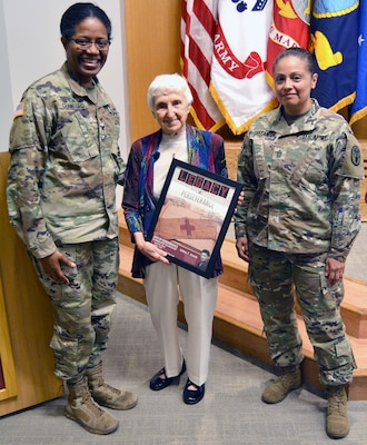 Army Col. Traci Crawford (left), Brooke Army Medical Center deputy commander, and Master Sgt. Nancy Castaneda, present Holocaust survivor Hanna Davidson Pankowsky (center) a token of appreciation April 24 during the Holocaust Days of Remembrance observance at Brooke Army Medical Center. Pankowsky shared her story of escaping Poland at 10 years old with her mother.
