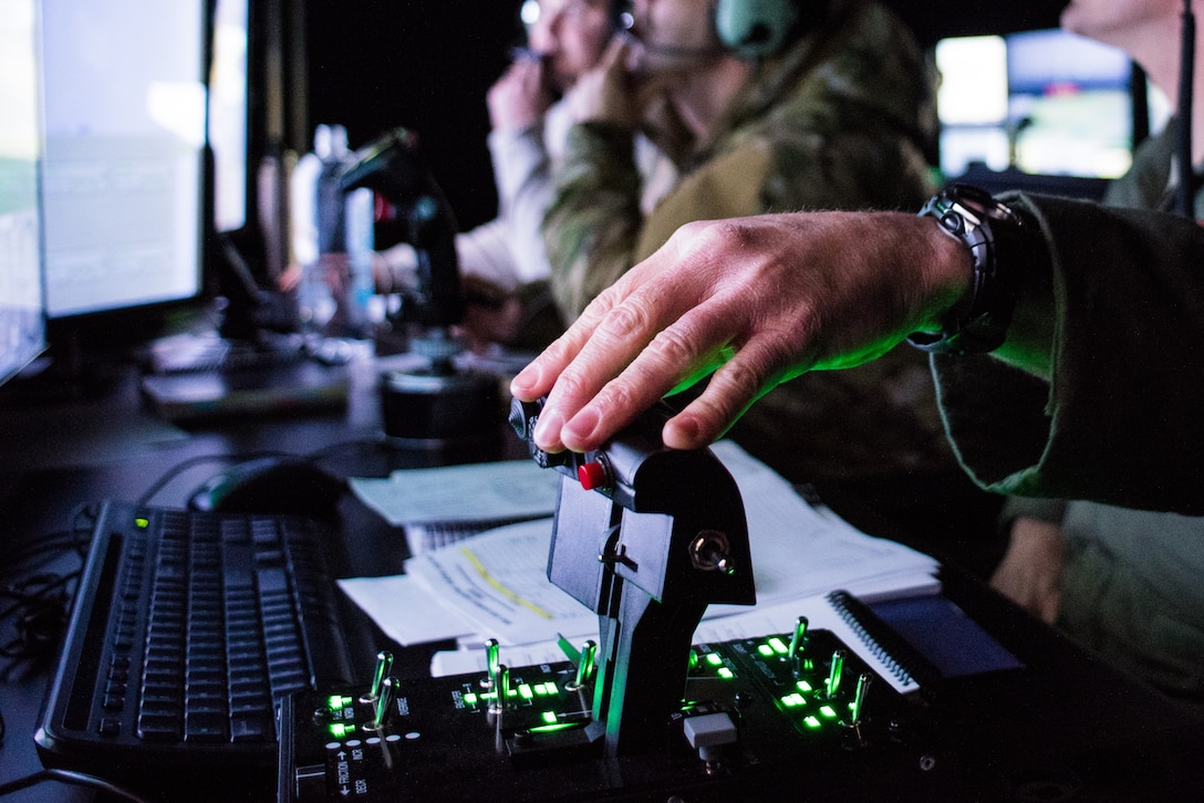 Lt. Col. Jason Smith, a pilot from the 301st Fighter Wing, Fort Worth, Texas, conducts a simulated flight mission while a tactical air control party specialist calls in an air strike during a simulated mission run by the 138th Combat Training Flight on an Air National Guard Advanced Joint Terminal Attack Controller Simulator at Will Rogers Air National Guard Base in Oklahoma City, Feb. 1, 2018. The simulator has saved the Air National Guard and Air Combat Command both time and money while ensuring the readiness of battlefield Airmen. (U.S. Air National Guard photo by Senior Airman Brigette Waltermire)