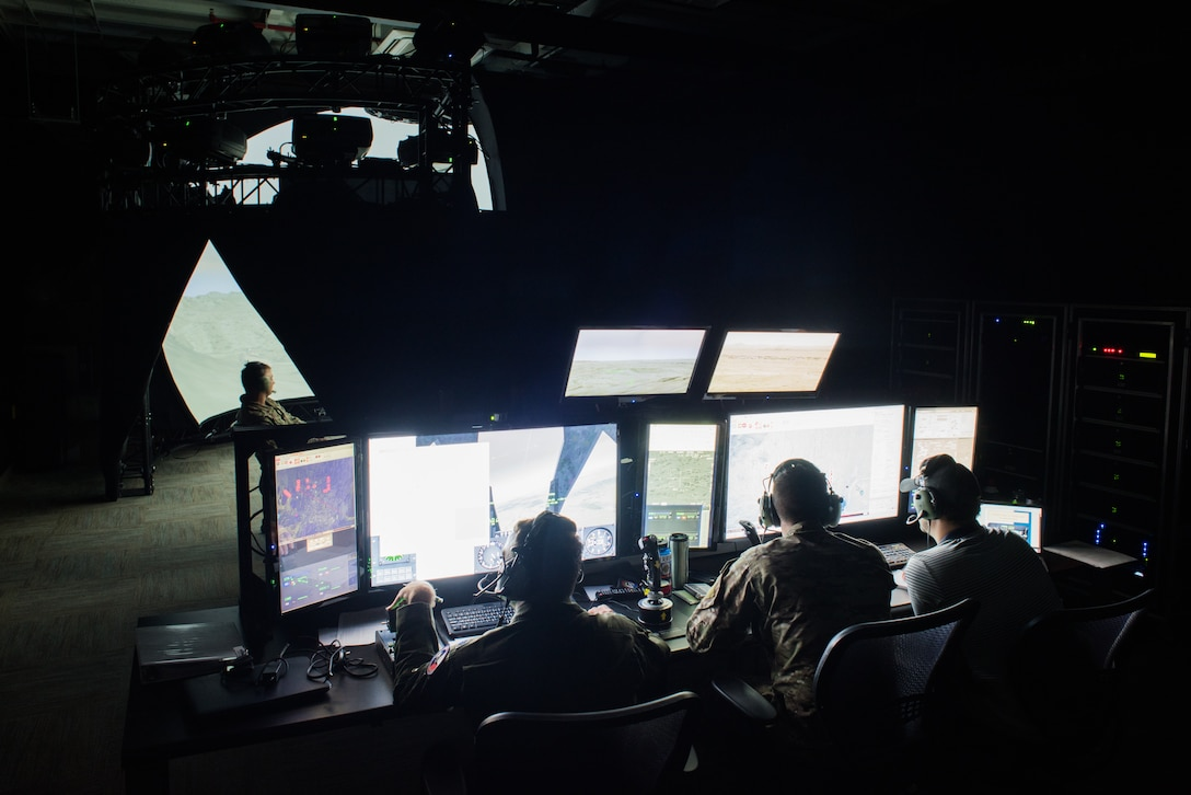 Instructors operate a 138th Combat Training Flight Air National Guard Advanced Joint Terminal Attack Control Simulator while a Tactical Air Control Party specialist calls in an airstrike during a simulated mission at Will Rogers Air National Guard Base in Oklahoma City, May 9, 2018. The simulator has saved the Air National Guard and Air Combat Command both time and money while ensuring the readiness of battlefield Airmen. (U.S. Air National Guard photo by Staff Sgt. Tyler Woodward)
