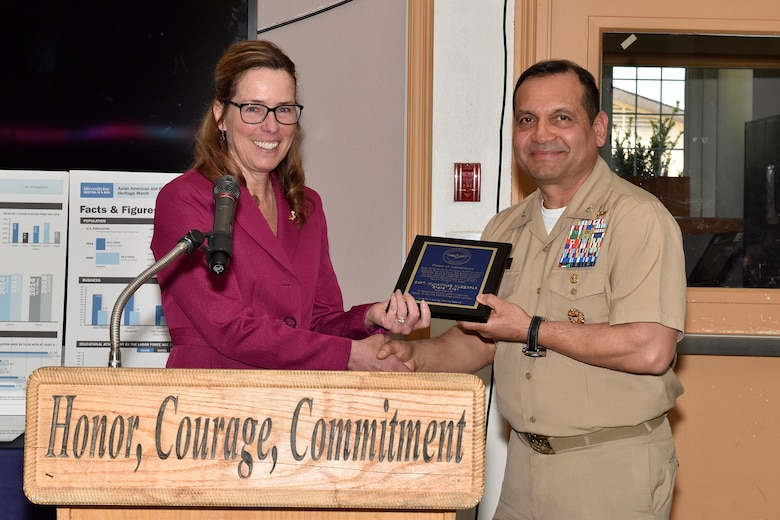 Kathleen P. Donnelly, director of the Naval Air Support Equipment and Aircraft Launch and Recovery Equipment Department, presents U.S. Navy Capt.