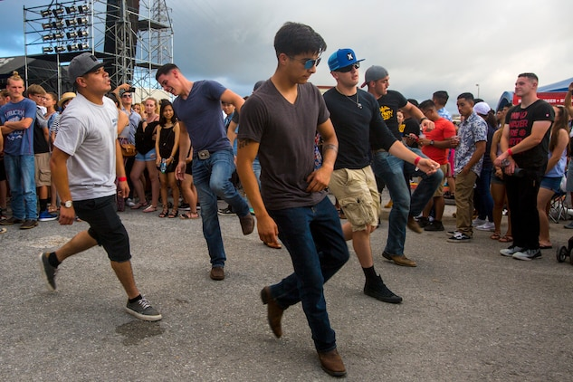 Marines line dance to a local band performance during Foster Fest May 12 aboard Camp Foster, Okinawa, Japan. The annual festival allowed members of the community to enjoy food, games and music. More than 13,000 people attended the two-day event.  (U.S. Marine Corps photo by Pfc. Nicole Rogge)