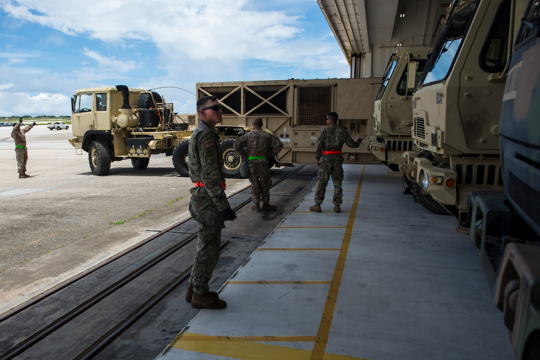 Soldiers assigned to the 94th Army Air and Missile Defense Command, Task Force Talon, marshal a vehicle into position inside a hangar during a Typhoon readiness exercise, 9 May, 2018, on Andersen Air Force Base, Guam. The exercise helped the soldiers practice the close coordination and different procedures they may have to implement to protect assets and personnel in the event of severe weather. (U.S. Air Force photo/Senior Airman Zachary Bumpus)