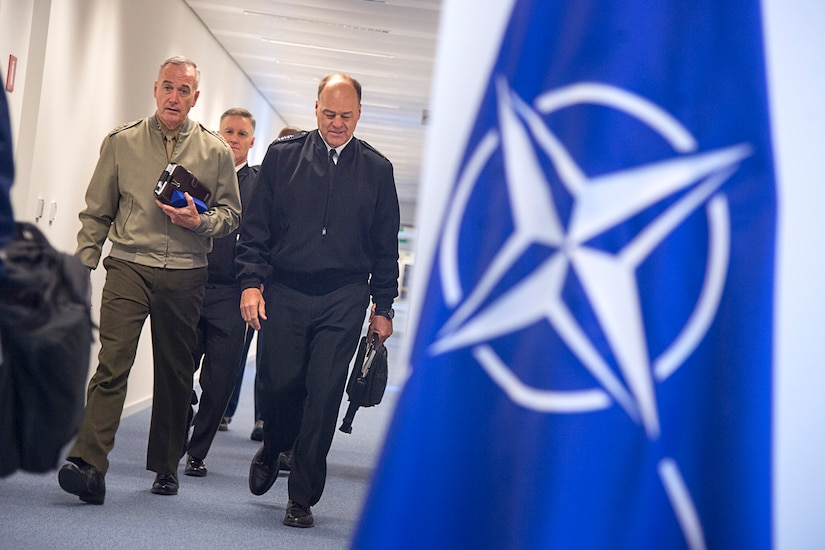 Two military leaders walk down a hallway with a NATO flag on the side.