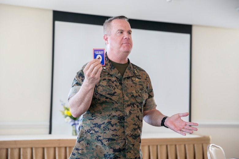Patrick Smith, senior chaplain, Marine Corps Air Station New River, displays a commemorative pin to the attendees during the National Day of Prayer at the Officers' Club on MCAS New River, May 3.  The National Day of Prayer is open to all people of all faiths to pray for the nation. (U.S. Marine Corps photo by Lance Cpl. Nicholas Lubchenko)