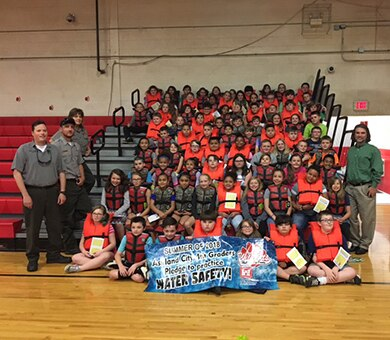 """Park Rangers pose with students wearing their life jackets at Ashland City Elementary School in Ashland City, Tenn., May 10, 2018. The U.S. Army Corps of Engineers Nashville District park rangers at Cheatham Lake engages students on the importance of water safety to culminate the """"2018 Summer Pledge to Practice Water Safety."""" (Photo by Chip Roney)"""