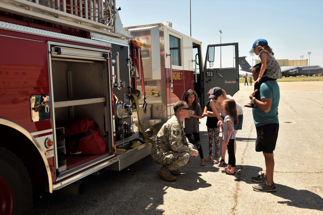 U.S. Air Force Tech. Sgt. Andrew Weertman, 433rd Civil Engineer Squadron assistant chief of operations, describes the job and equipment of firefighters beside Fire Engine 7 to Kim Martinez, Master Sgt. John Martinez, 433rd Aeromedical Evacuation Squadron AME examiner, and their children during the annual 433rd Airlift Wing Family Fun Day May 6, 2018, at Joint Base San Antonio-Lackland, Texas. Other options at the event included a dunk tank, bouncy houses, several open aircraft and more. (U.S. Air Force photo by Staff Sgt. Lauren M. Snyder)