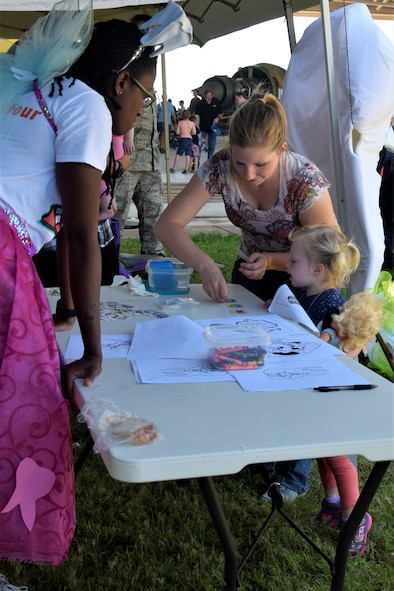 U.S. Air Force Tech. Sgt. Rachel Crabb, 433rd Aerospace Medicine Squadron dental technician, helps her daughter Rebecca, 2, choose and apply a dental-themed temporary tattoo at the 433rd Airlift Wing Family Fun Day May 6, 2018, at Joint Base San Antonio-Lackland, Texas. One of the goals of the annual event was to show family members what the units do, and there were several displays, such as dental, highlighting different jobs within the wing. (U.S. Air Force photo by Staff Sgt. Lauren M. Snyder)