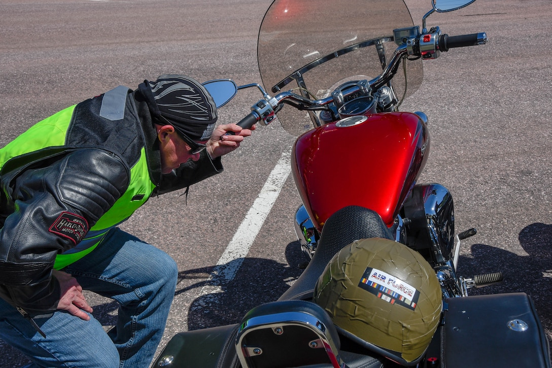 Master Sgt. Rick Vandenhoek, 114th Fighter Wing motorcycle mentor, examines an Airman's motorcycle before the mentorship ride at Joe Foss Field, S.D.