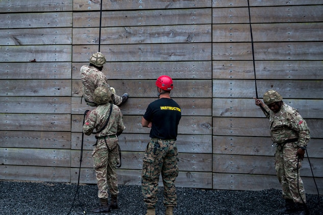 Soldiers of the Royal Bermuda Regiment train on rappelling as Capt. Mark Deal, ropes and recovery officer in charge for Expeditionary Operations Training Group, II Marine Expeditionary Force, supervises the Soldiers belaying at Stone Bay on Marine Corps Base Camp Lejeune on May 8, 2018. The regiment was at MCB Camp Lejeune for a two week evolution, the Junior Noncommissioned Officer Cadre, which includes scenario-based exercises, rappelling, section attacks and section battle drills. (U.S. Marine Corps photo by Lance Cpl. Dominique Fisk)