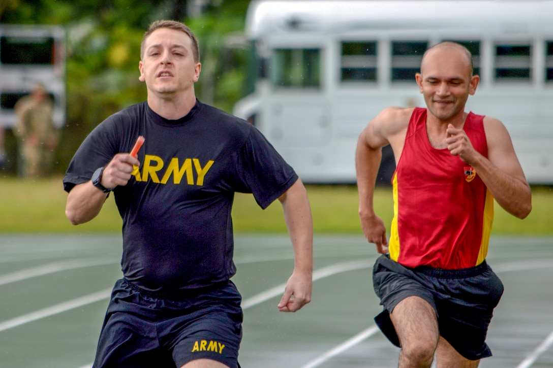 A U.S. and a Singaporean soldier run on a track.