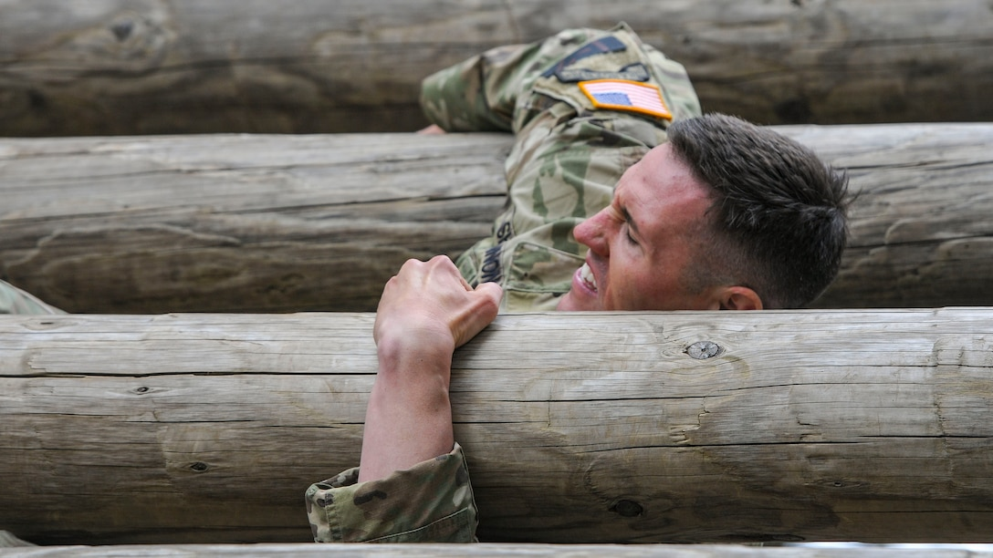 A soldier holds himself up on an obstacle course.