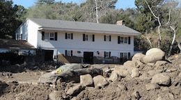 A house is seen caked inside and out with mud, while a destroyed vehicle and a pile of debris sits in the front yard following a Jan. 9 mudslide in Montecito, California, a community within Santa Barbara County.