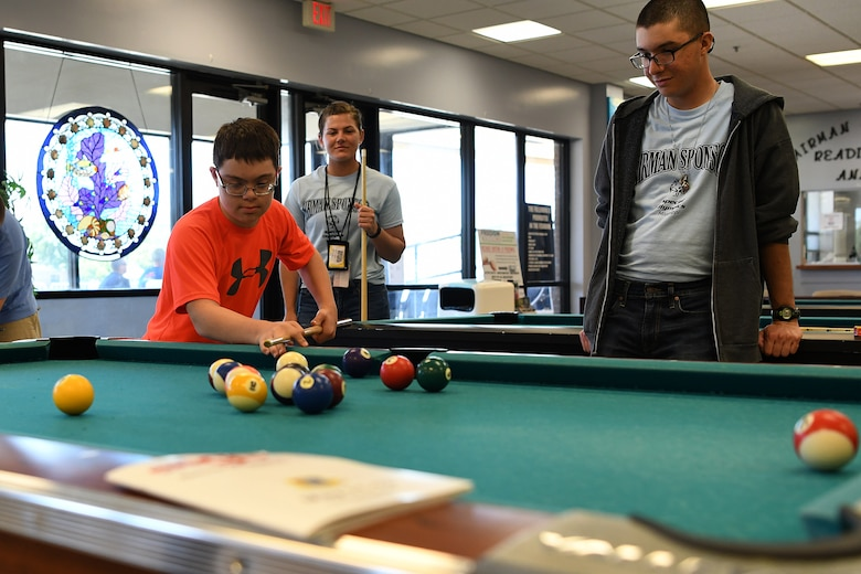 Easton Slutz, District 5 Special Olympics Mississippi athlete, plays pool with U.S. Air Force Airmen Kaimryn Hursch and Gabriel Agostini-Mesa, 336th Training Squadron students, during SOMS in the Levitow Training Support Facility at Keesler Air Force Base, Mississippi, May 11, 2018. On the first day of SOMS, Slutz, Agostini-Mesa and Hursch spent the day getting to know each other by playing pool, basketball and dominoes. (U.S. Air Force photo by Airman 1st Class Suzie Plotnikov)