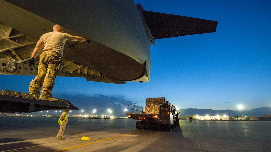 Heavy machine moves near an aircraft.