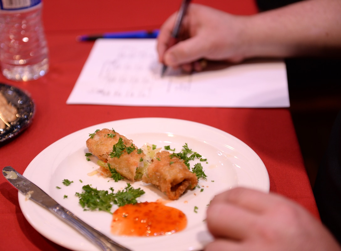 A judge writes down his score after tasting an appetizer during the Taste of Luke cooking competition at Luke Air Force Base, Ariz., May 9, 2018. Food was judged based on criteria such as presentation, flavor, and incorporation of special ingredients. (U.S. Air Force photo by Senior Airman Ridge Shan)