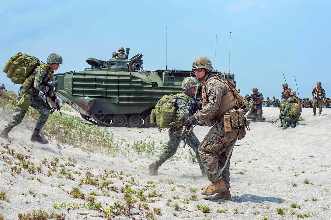 U.S. and Philippine service members run on the beach near heavy equipment.