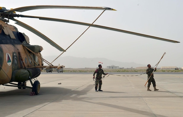 An Afghan Air Force maintenance professional tie down the propellers of an Mi-17 at Kandahar Airfield, Afghanistan, May 7, 2018. This was one of six Mi-17s that received damage from aggressors so far this year, but after extensive sheet metal repairs, the aircraft are all continuing operational missions. (U.S. Air Force photo/1st Lt. Erin Recanzone)