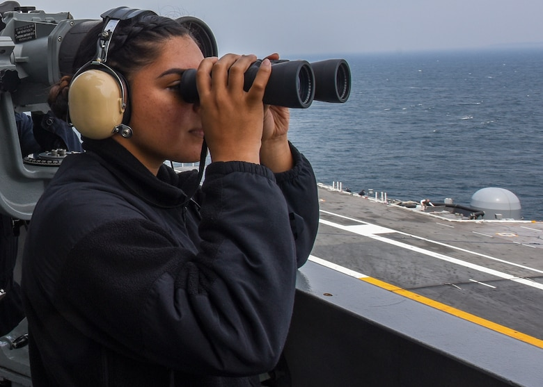 Operations Specialist Seaman Apprentice Stephanie Cruz, from San Diego, California, and Operations Specialist 3rd Class James Harrell, from St. Louis, Illinois, stand port-side lookout on vultures' row of the Navy's forward-deployed aircraft carrier, USS Ronald Reagan (CVN 76), as the ship returns to Commander, Fleet Activities Yokosuka following sea trials. Ronald Reagan, the flagship of Carrier Strike Group 5, provides a combat-ready force that protects and defends the collective maritime interests of its allies and partners in the Indo-Asia-Pacific region.