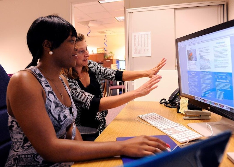 Tiara Slater (left), a Thurgood Marshall College Fund student, and AFRL/RI's Keri Burkhardt work on a marketing project at Rome Laboratory. (Photo from Rome Laboratory)