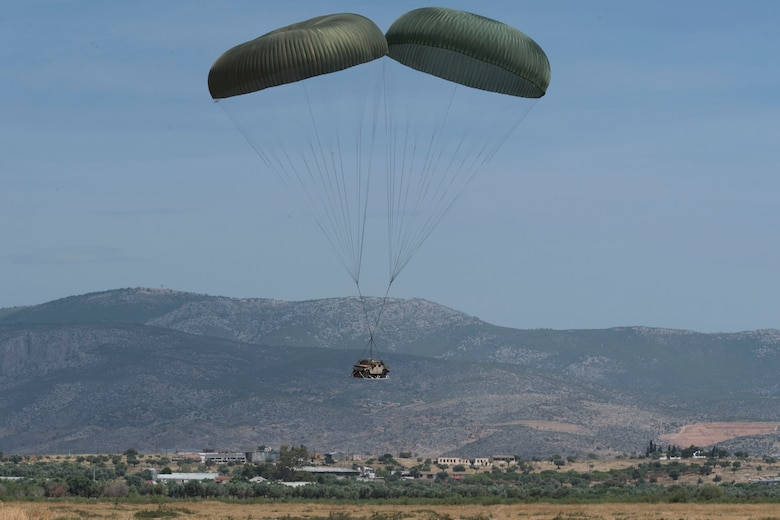 A U.S. Humvee rigged to parachutes floats to the ground during an exercise Stolen Cerberus V training mission over Megara Drop Zone, Greece, May 15, 2018. Hellenic riggers worked with U.S. Air Force joint airdrop inspectors to get the Humvee properly rigged to drop. (U.S. Air Force photo by Senior Airman Devin M. Rumbaugh)