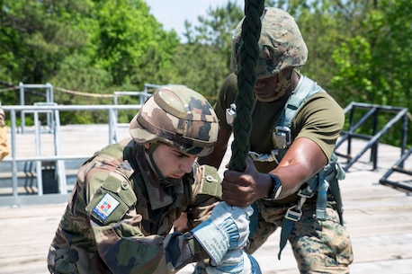 A U.S. Marine with II Marine Expeditionary Force Information Group and a French Marine prepare to fast rope from a rappel tower during exercise Burmese Chase at Camp Lejeune, N.C., May 10, 2018. Burmese Chase is an annual U.S. led multi-lateral exercise that enables U.S. Marines to train with NATO allies and partner nations. This exercise strengthens partner nation security as well as enhances force readiness. (U.S. Marine Corps photo by Lance Cpl. Caleb Maher)