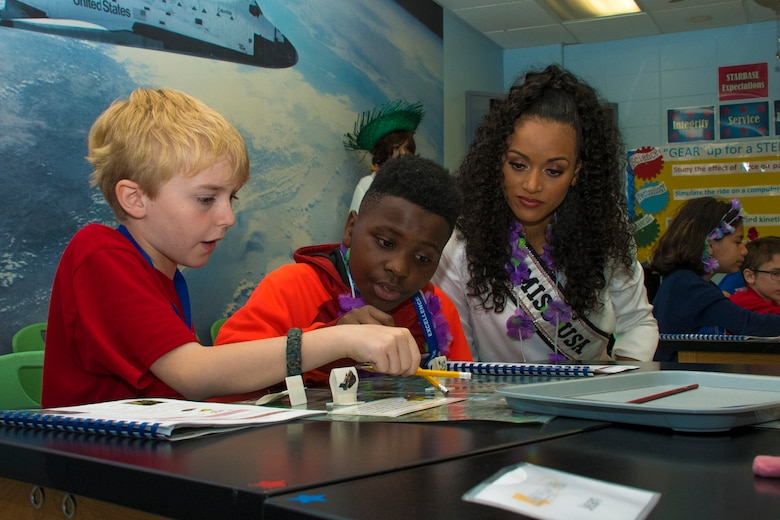 Kara McCullough, Miss USA 2017, helps students with their project during her visit to STARBASE Louisiana on Barksdale Air Force Base, Louisiana, May 15, 2018.