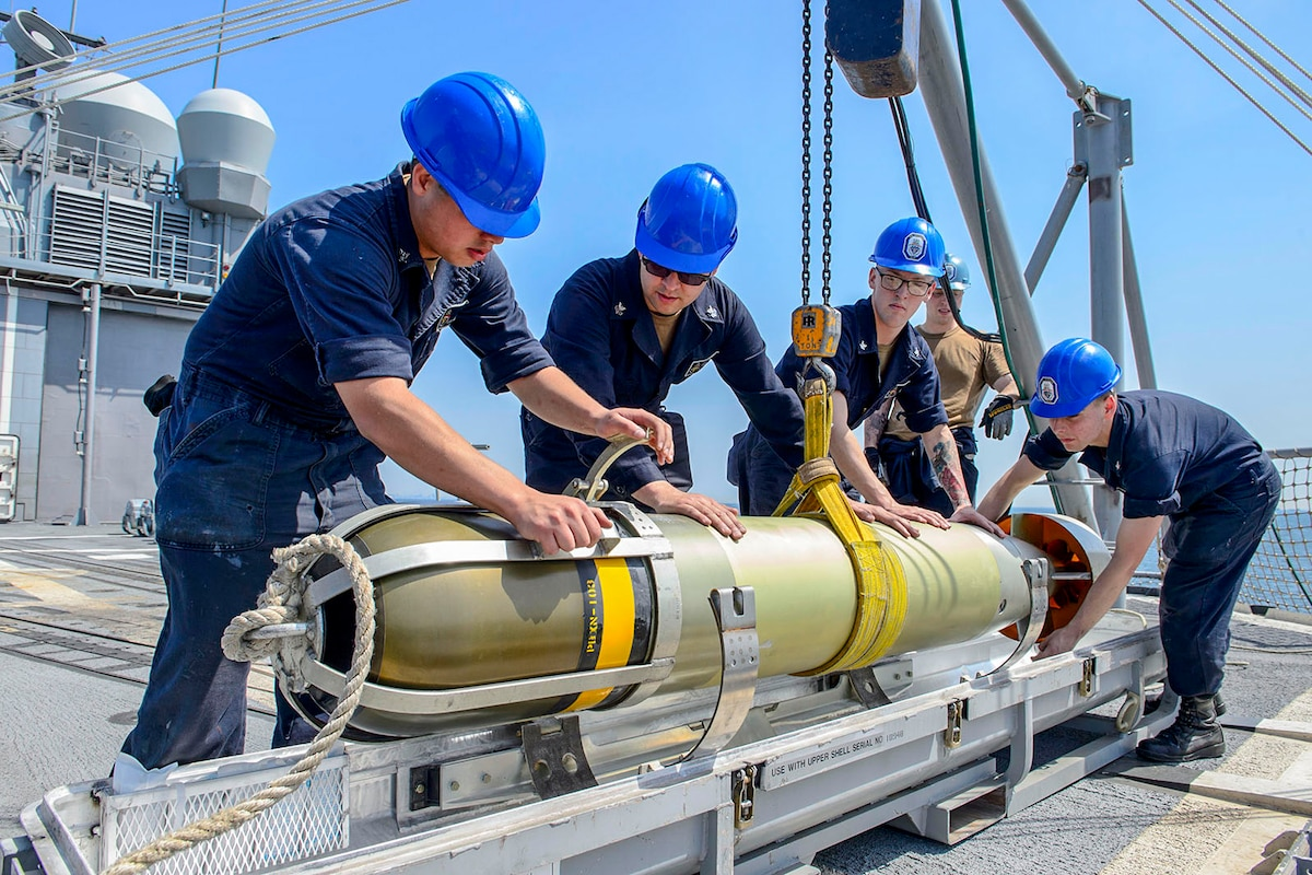 Four sailors in blue hardhats secure a torpedo to a platform on a ship's deck.
