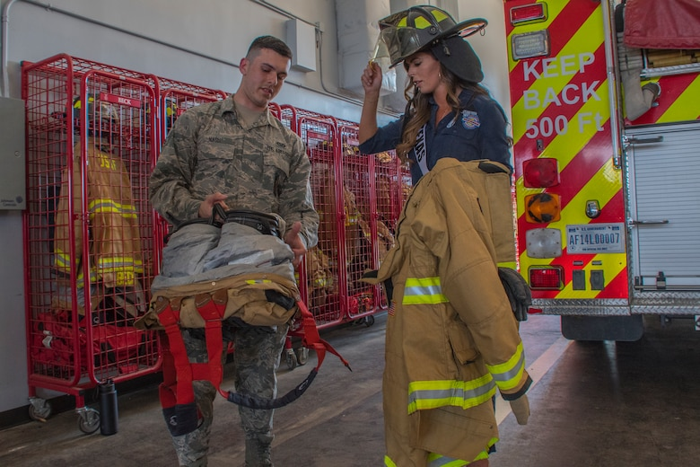 U.S. Air Force Airman 1st Class Austin Nash, a 2nd Civil Engineer Squadron firefighter, shows Logan Lester, Miss Texas USA 2018, fire-fighting gear at Barksdale Air Force Base, Louisiana, May 15, 2018.