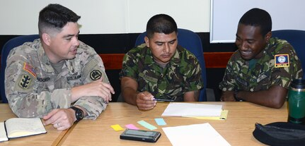 Maj. Terry Vallarautto (left), U.S. Army Louisiana National Guard, participates in a table top exercise with Sgt. Robert Jones (center) and soldiers from the Belize Defence Force during an Energy and Water Conservation Policy Subject Matter Exchange in Belize City May 8.