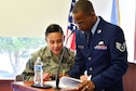 Staff Sgt. Lina Torres, 70th Intelligence, Surveillance and Reconnaissance Wing Protocol non-commissioned officer in charge, reviews a script with Staff Sgt. Marcus McCall, 70th ISRW chaplain's office NCOIC for resource management, before a retirement ceremony April 20, 2018, Fort George G. Meade, Maryland. McCall is part of the 2017 Air Force Best Small Chapel team. (U.S. Air Force photo by Staff Sgt. Alexandre Montes)
