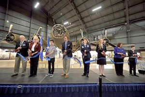 The ribbon is cut to the B-17F Memphis Belle Exhibit during a public ceremony on May 17, 2018: (left to right) Brian Pecon (Memphis Belle Memorial Association President), Col. Susan Richardson, USAF (Ret) (Chairman of the Air Force Museum Foundation Board of Trustees), Thomas Harrison (Student from England), Lt. Gen. Jack Hudson, USAF (Ret) (Museum Director), Lt. Gen. Jacqueline Van Ovost (Air Force Director of Staff), Ms. Grace Ojala (Winner of the Museum's Writing Competition), Krista Strider (Museum Deputy Director), Joshua Cahoon (Winner of Museum's Aviation Art Competition).