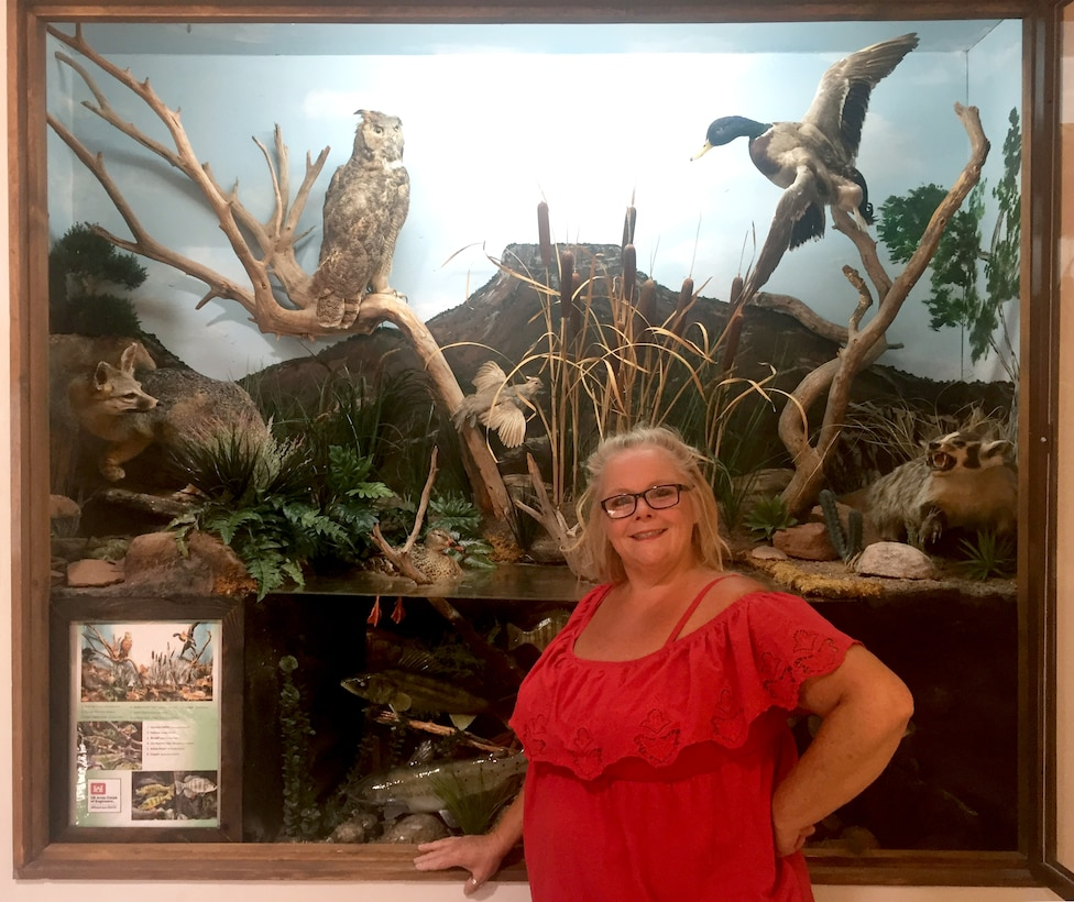 Janice Ducrepont stands in front of the visitor center's wildlife display, May 8, 2018. She volunteered her painting skills to paint the scenic background in the display.