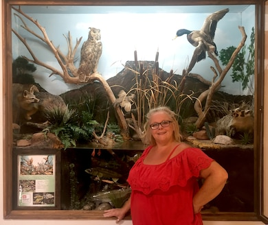 Janice Ducrepont stands in front of the Abiquiu Lake visitor center's wildlife display, May 8, 2018. She volunteered her painting skills to paint the scenic background in the display.