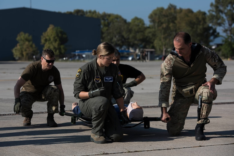 U.S. Air Force Staff Sgt. Rachel Wilson (center), 86th Aeromedical Evacuation Squadron aeromedical evacuation technician, instructs Hellenic service members on the procedure of lifting a patient during an exercise Stolen Cerberus V training mission at Elefsis Air Base, Greece, May 9, 2018. Exercises such as these improve joint aeromedical evacuation operations and procedures. (U.S. Air Force photo by Senior Airman Devin M. Rumbaugh)