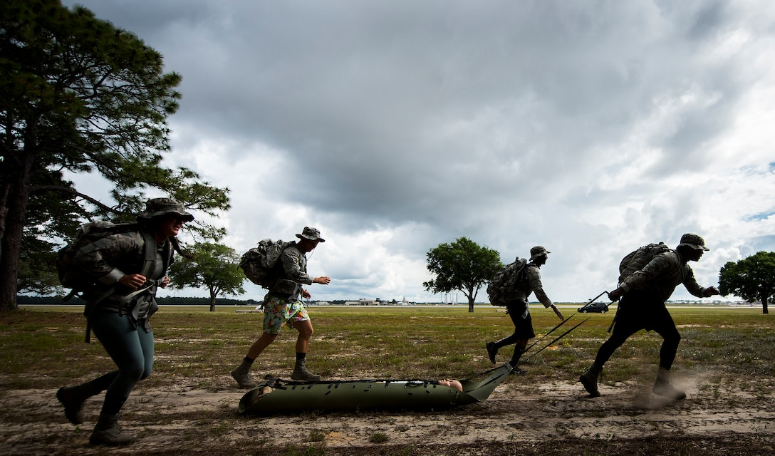 A 96th Security Forces Squadron (SFS) team runs with a simulated victim during the new Warrior Challenge event at Eglin Air Force Base, Fla., May 16, 2018. The Warrior Challenge is a physical activity event created by 96th SFS to highlight security training efforts during Police Week. Teams began a ruck march that led to physical activities like self-aid and buddy care, disassembling and reassembling a weapon and more. (U.S. Air Force photo by Samuel King Jr.)