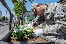 Staff Sgt. Justin Minimo, 374th Communications Squadron Operations Flight client systems technician craftsman, secures the soil around a flower during the Fussa Beautification Project just outside of Yokota Air Base in Fussa, Japan, May 14, 2018.