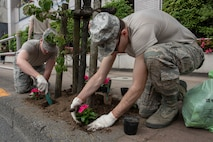 Airman 1st Class Hunter Lobb, 374th Communications Squadron Operations Flight client systems technician apprentice, left, and Staff Sgt. Walter Voner, 374 CS OF client systems technician craftsman, right, work together to plant flowers for the Fussa Beautification Project outside of Yokota Air Base, Japan in Fussa May 17, 2018.