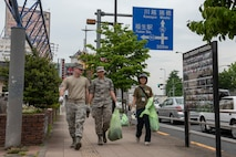 Volunteers from Yokota Air Base, Japan and the city of Fussa carry bags of weeds to be disposed of immediately following the Fussa Beautification Project in Fussa, May 17, 2018.