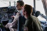 Brig. Gen. Yousef Al Kuwari, the Qatar Defense Attaché, laughs with a pilot from the 167th Airlift Wing as he grabs the controls of a C-17 Globemaster III May 14, 2018 at McLaughlin Air National Guard Base, Charleston, W.Va. Members of the Qatar Defense Attaché Office of the Qatar Embassy in the United States, representing Qatar's Ministry of Defense, discussed developing further relationships between Qatar and West Virginia during their visit. (U.S. Air National Guard Photo by Airman 1st Class Caleb Vance)
