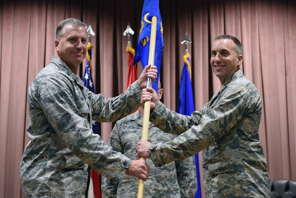 U.S. Air Force Col. David Eaglin, 39th Air Base Wing commander, presents the guidon to Col. Christopher Estridge, 39th Medical Group commander, during a change of command ceremony at Incirlik Air Base, Turkey, May 18, 2018.