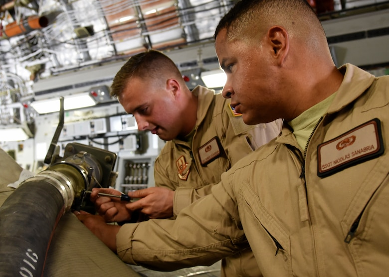 Airman 1st Class Tanner O'Laughlin (left) and Staff Sgt. Nicolas Sanabria (right) secure a fuel hose to a 2,800 gallon fuel bladder at Al Udeid Air Base, Qatar, May 11, 2018. This delivery is the first of its kind in more than a year and a half. (U.S Air Force photo by Staff Sgt. Enjoli Saunders)