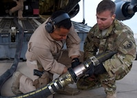 Staff Sgt. Nicolas Sanabria (left) and Tech. Sgt. Stuart Burrus (right) ensure a fuel distribution hose is properly connected in an undisclosed location in Southwest Asia, May 11, 2018. This delivery is the first of its kind in more than a year and a half. (U.S Air Force photo by Staff Sgt. Enjoli Saunders)