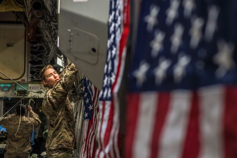 Senior Airmen Christa Stankovic, 816th Expeditionary Airlift Squadron, hangs U.S. flags onboard a C-17 Globemaster III during an airdrop mission over Afghanistan, May 10, 2018. The primary mission of the C-17 is to provide rapid strategic delivery of troops and various types of cargo to bases throughout the U.S. Central Command area of responsibility. (U.S. Air Force photo by Staff Sgt. Keith James)