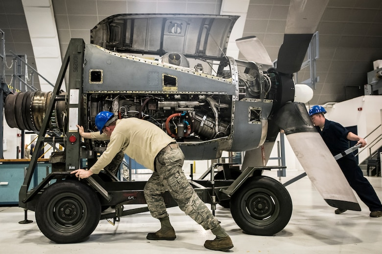 Staff Sgt. Ryan Morahan, Senior Airman Matthew Boals and Airman 1st Class Noah, 179th Airlift Wing maintenance members, move an engine into place before placing it back onto a C-130H Hercules, May 10, 2018. The Airmen have inspected and maintained the engine during an isochronal inspection.  (U.S. Air National Guard photo by Capt. Paul Stennett)